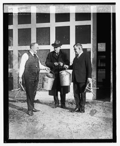 Johnson (left) and Wallace (right) presenting their milk buckets to Maj. Gen. Bliss (center), who is looking at this watch.