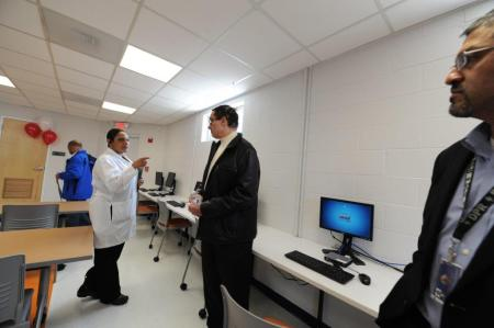 Mayor Gray inspecting new computers in the community room.