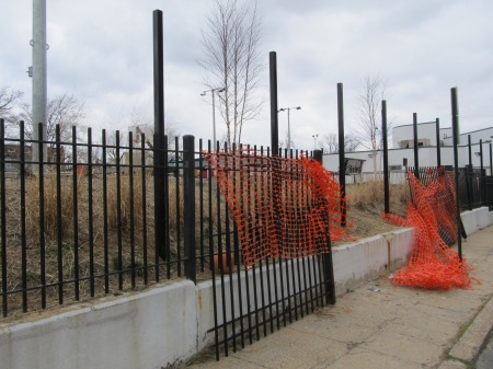 The new, taller fence being installed along Otis Place.