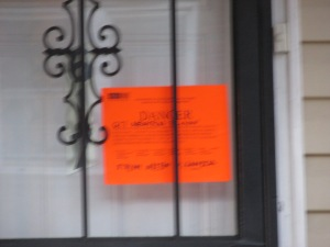 Danger sticker on front of 617 Newton Place, NW.