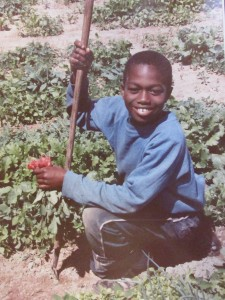 Twin Oaks Youth Gardener with radishes, ca. 1970s
